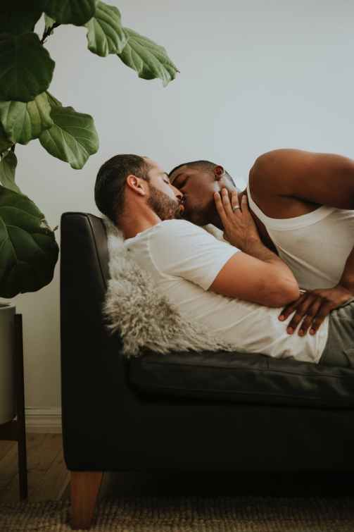 two men kissing each other on couch