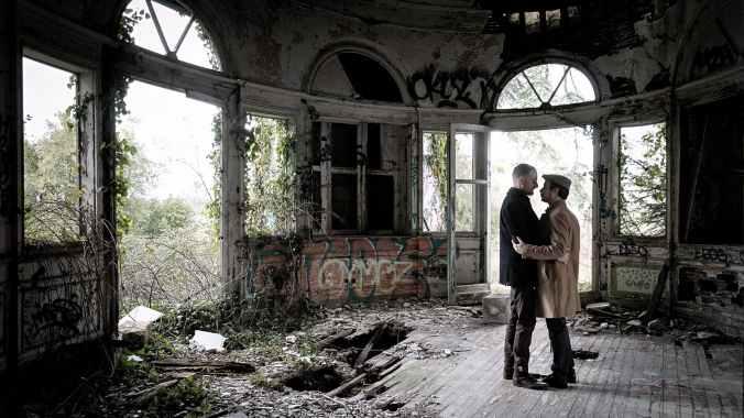 two men standing on brown floor inside wrecked building