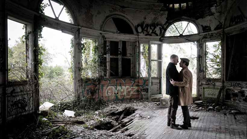 two men standing on brown floor inside wrecked building