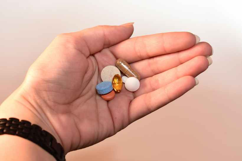 person holding medication pill and capsules