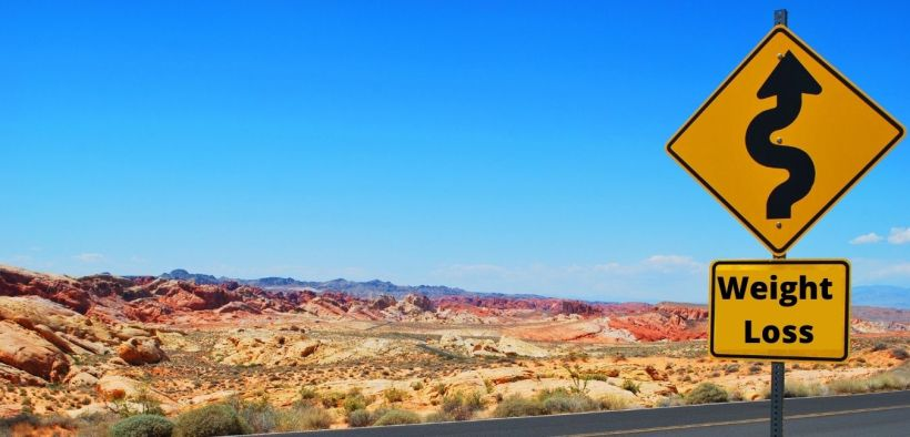 road sign with a desert in the background. sign shows a cure road and reads weight loss
